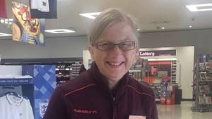 Eine grauhaarige Frau mit Brille lächelt glücklich in die Kamera. Sie ist in einem Sainsbury's Supermarkt.