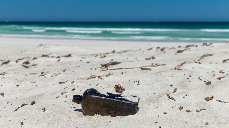 Eine Flasche liegt im Sand eines Strandes - Es soll sich um die deutsche Flaschenpost handeln, die nach 132 Jahren in Australien