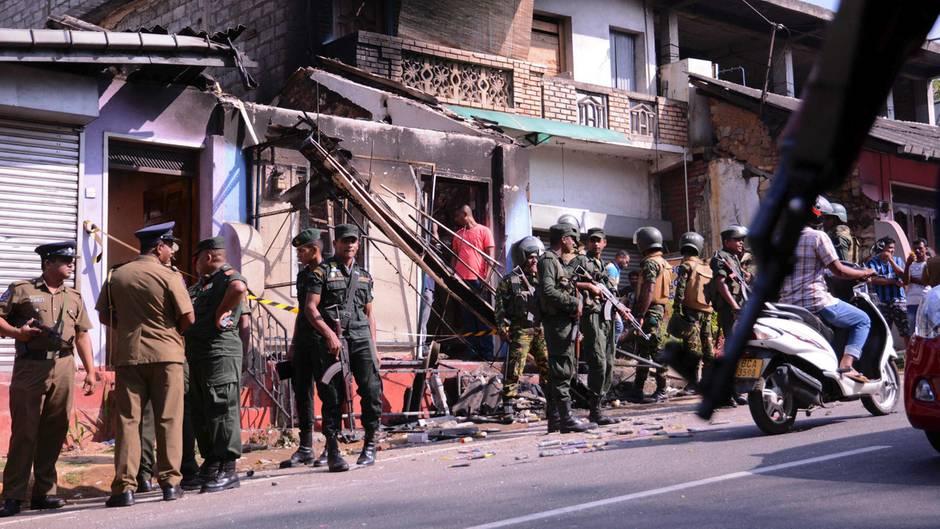 Polizisten und Soldaten stehen in einem Vorort von Kandy, Sri Lanka vor einem verwüsteten Gebäude