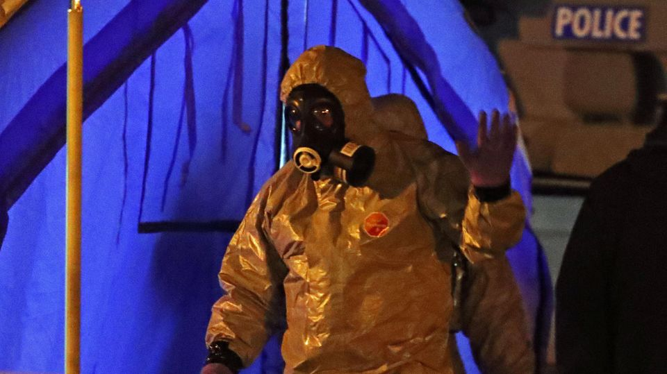 Ermittler tragen außerhalb eines Zeltes Schutzanzüge