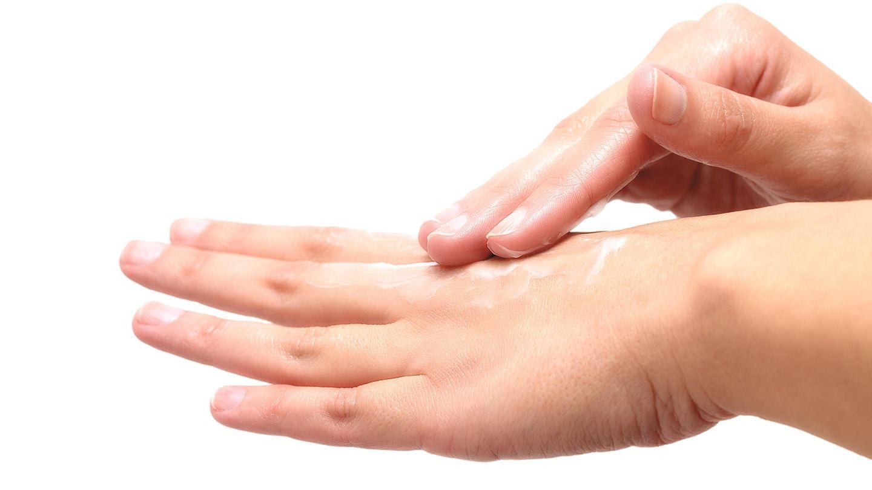 Eine Frau cremt sich die Hände ein