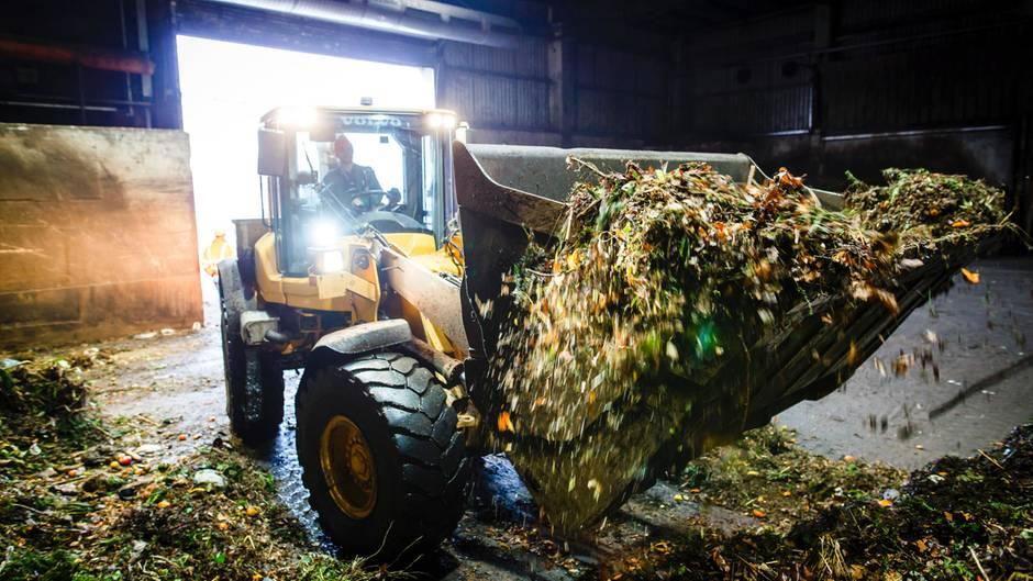Gelber Bagger in Biogasanlage mit Biomüll auf der Schaufel