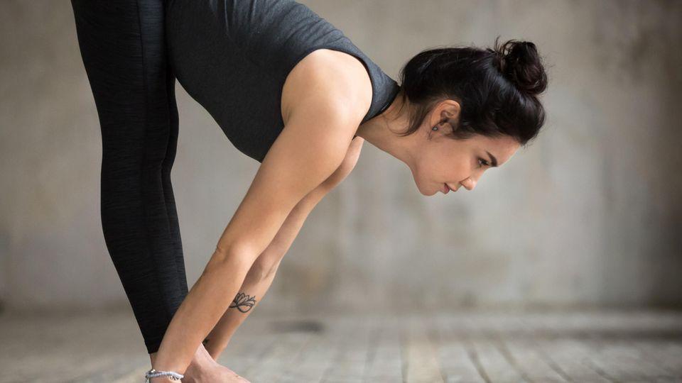 Junge Frau macht Yoga-Übung auf Yoga-Matte