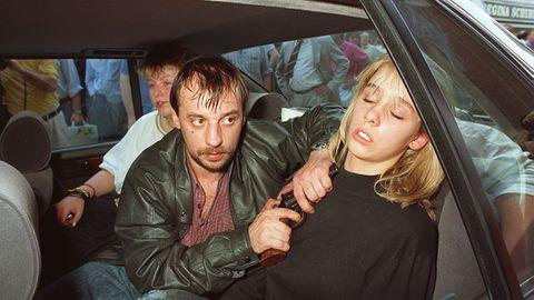 Drei Menschen auf der Rückbank eines Autos: In der Mitte sitzt Dieter Degowski und hält Silke Bischoff eine Waffe an den Kopf