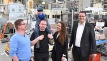 Drei Männer und eine Frau stehen lachend in einer Fabrik. Ein Mann trägt ein Kind auf der Schulter, das den Daumen hoch zeigt.