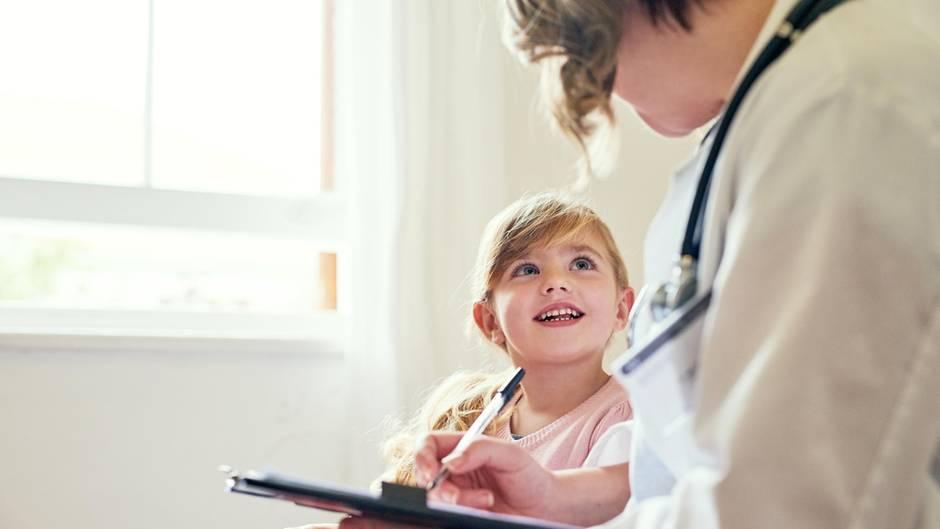 Kind sitzt neben einem Arzt und lächelt