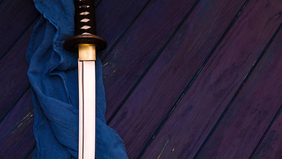 Ein Samurai-Schwert liegt auf einem blauen Tuch
