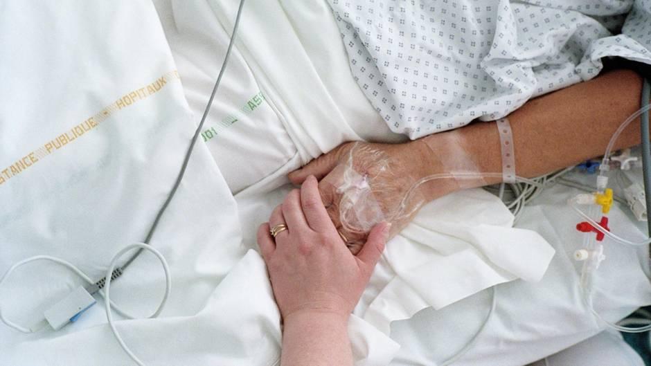Eine Krankenschwester hält die Hand eines Patienten.