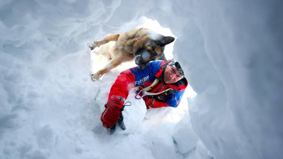 Ein Retter sucht mit seinem Hund bei einer Übung nach potenziellen Lawinenopfern