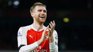 Per Mertesacker steht im rot-weißen Arsenal-Trikot nach Abpfiff auf dem Rasen, lächelt und applaudiert.