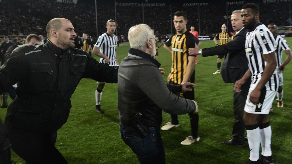 Ivan Savvidis (m.), Präsident von Paok Saloniki, läuft beim griechischen Derby zwischen Paok und AEK Athen mit einer Pistole am Gürtel aufs Spielfeld.
