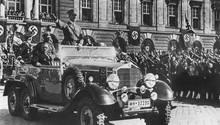 Am 14. März 1938 jubeln Österreicher in Wien Adolf Hitler zu. Neben ihm sitzt der österreichische Kanzler Arthur Seyss-Inquart im Parade-Wagen.