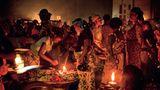 Frauen verkaufen Gemüse im Dorf Glo im Süden Benins. Die einzige Lichtquelle sind kleine Lampen mit teurem Petroleum: Die Menschen in Benin geben im Schnitt ein Fünftel ihres Einkommens für Licht aus