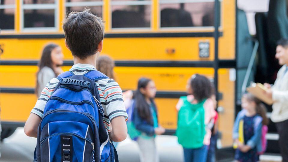 Kinder vor einem gelben Schulbus