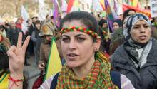 Eine Demonstrantin mit gelb-rot-grünem Stirnband und Halstuch zeigt mit ihrer rechten Hand ein Peace-Zeichen