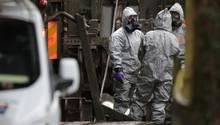 Mitglieder der Spurensicherung stehen in Schutzkleidung in der Nähe des Tatorts im Fall Skripal
