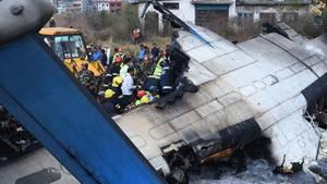 Ein ausgebranntes und seitlich aufgerissenes Flugzeug liegt auf dem Flughafen von Kathmandu, Nepal, auf dem Dach