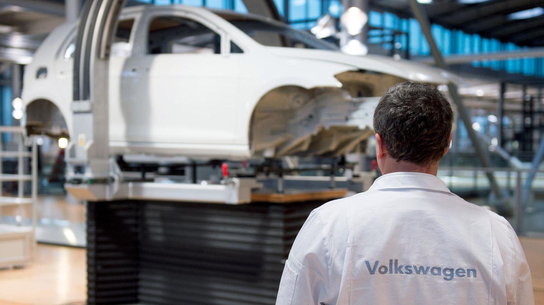 Ein VW-Mitarbeiter steht vor einem unfertigen VW-Auto