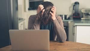 Eine Frau sitzt am Computer und ärgert sich über Crypto-Jacking