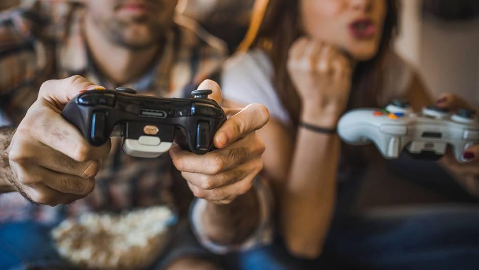 Ein Mann und eine Frau spielen Videospiele. Im Vordergrund ist ein Controller