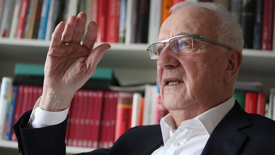 Während Fritz Pleitgen spricht, sitzt er vor einem Bücherregal, dessen Inhalt von seinem Reporterleben zeugt.
