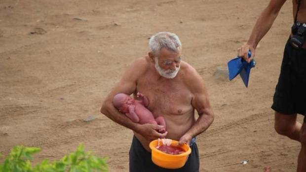 Der Arzt, der während der Wassergeburt anwesend war, trägt das Baby und die noch mit dem Kind verbundene Plazenta an Land