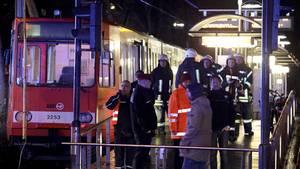 Feuerwehrleute stehen an der Haltestelle in der Kölner Innenstadt, an der zwei Straßenbahnen zusammengestoßen sind
