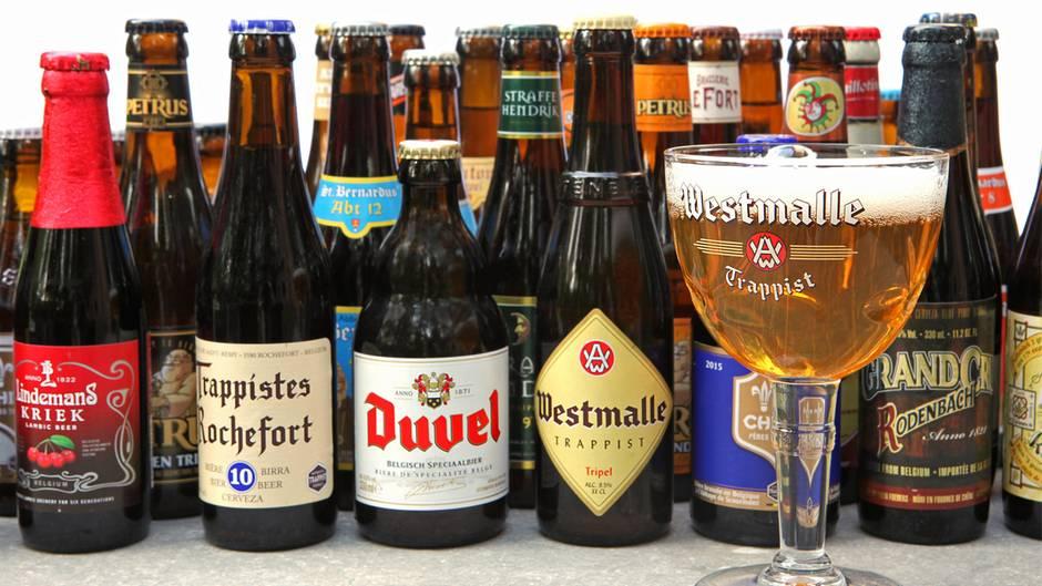 Ein Bierglas steht vor unterschiedlichen Biersorten aus Belgien