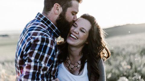 Ein Paar küsst sich auf einer Wiese