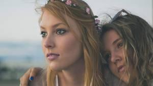Millennials: Zwei junge Mädchen mit Blumen in den Haaren umarmen sich