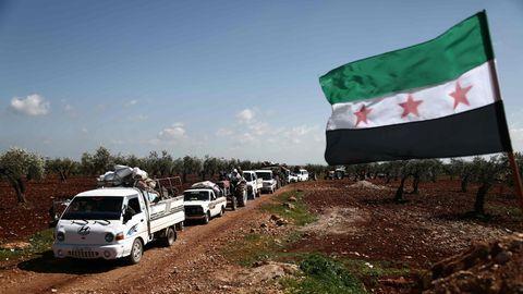 Auf einem Feldweg rollt eine Kolonne aus Autos, Transportern und Traktoren aus der umkämpften Stadt Afrin heraus