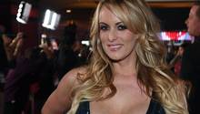 Eine Frau mit langen blonden Haaren und tief ausgeschnittenem Pailetten-Kleid lächelt.