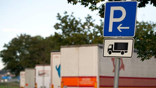 Geparkte Lastwagen stehen auf einem Autobahnrastplatz