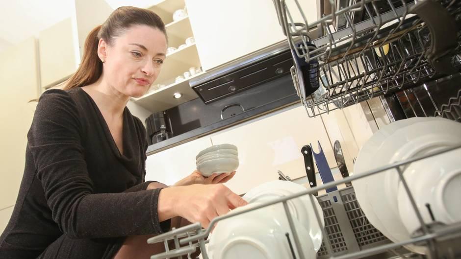 Eine Frau räumt eine Spülmaschine aus.