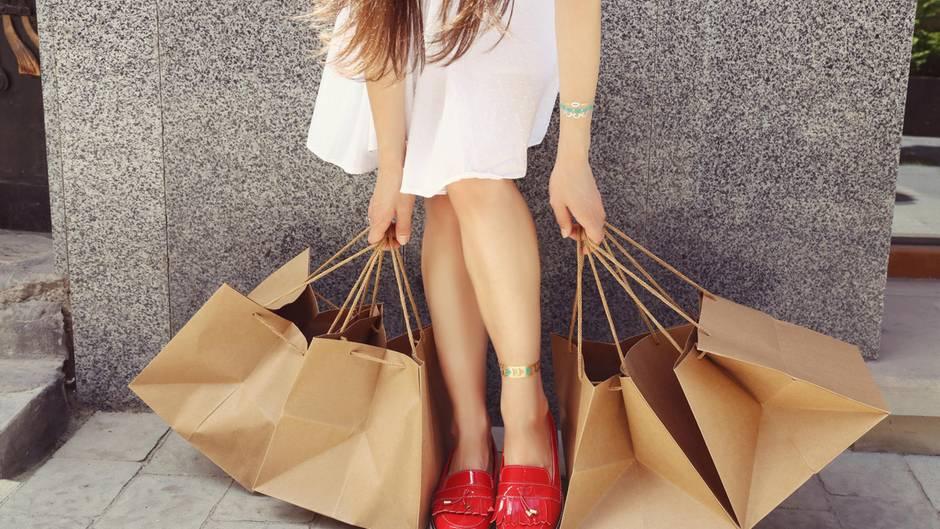 Ein Mädchen mit roten Schuhen bückt sich, um ihre Papiertragetaschen hochzuheben.