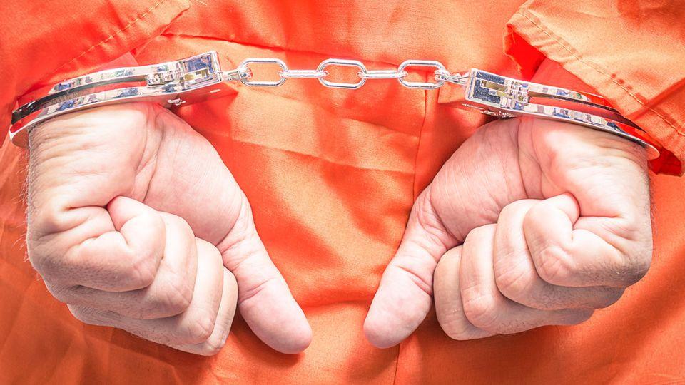Hinter dem Rücken gefesselte Hände eines Häftlings