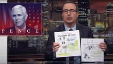 John Oliver sitzt im Anzug in der Kulisse seiner TV-Show und hält zwei fast identische Bücher in die Kamera