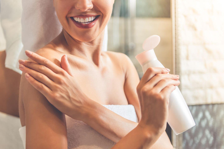 Eine Frau cremt sich mit einer Körperlotion ein
