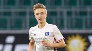Ein junger Mann mit dunkelblonden, hochgeföhnten Haaren läuft in weißem HSV-Trikot und roter Hose über einen Fußballplatz