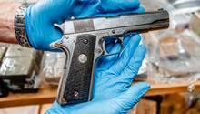 Eine Pistole wird in Händen mit Handschuhen gehalten
