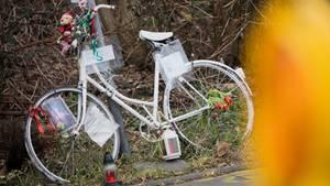 Ein komplett weißes Fahrrad mit Blumen, Kerzen und Stofftieren steht an einem Straßenschild