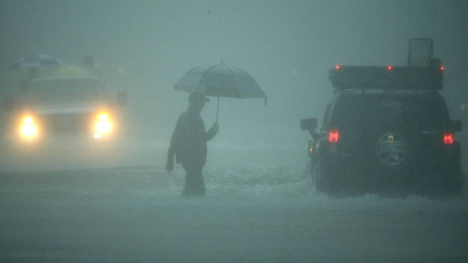 Ein Mann geht durch extremen Regen