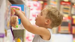 Ein Junge steht vor einem Regal voller Spielzeug