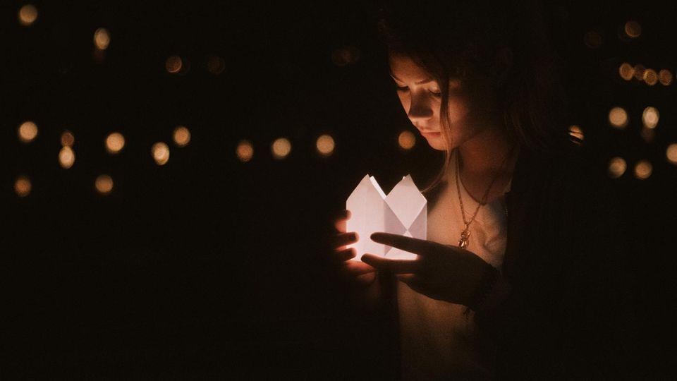 Eine junge Frau schaut in ein Kerzenlicht