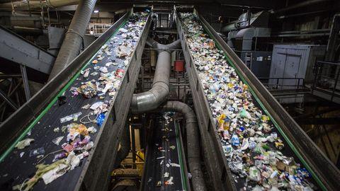 Förderbänder transportieren den Verpackungsabfall in die eigentliche Sortierhalle, einem fast apokalyptischen Ort: dunkel, stickig, laut, klebrig, gefährlich.