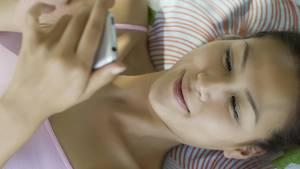Eine Frau im Bett hält ihr Smartphone in der Hand