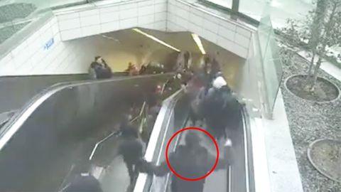 Ein Mann strauchelt und greift noch an die Handläufe der Rolltreppe