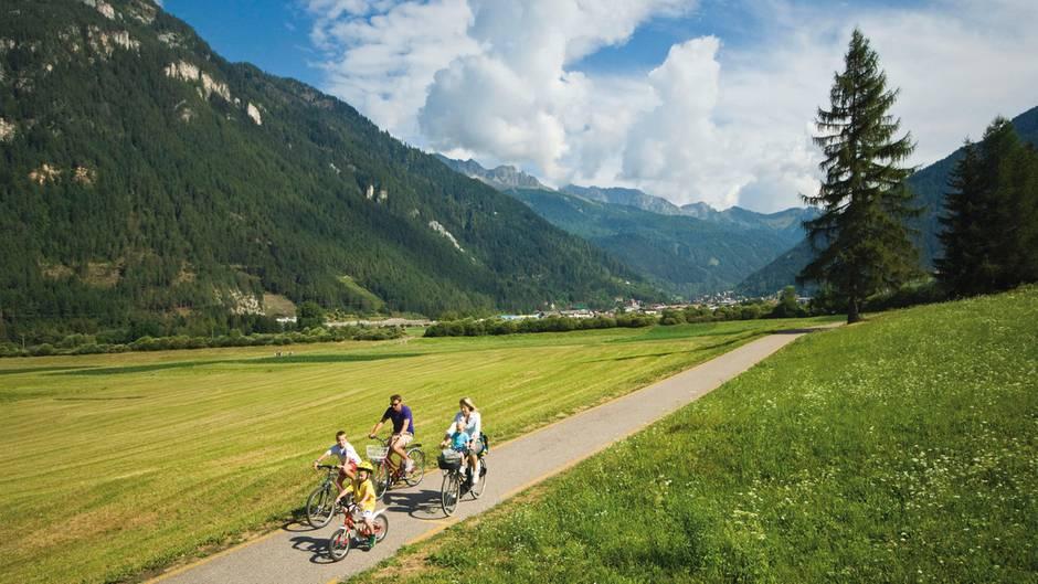 Auf zwei Rädern im Sattel  Fahrradfahren vor grandioser Kulisse: Im Trentino gibt es ein dichtes Wegenetz von Fahrradrouten. Dabei geht es mit dem Mountainbike nicht nur über Stock und Stein, sondern auch auf ausgeschilderten Wegen durch flache Täler - ohne Autoverkehr auf der Strecke, wie hier im Val di Fiemme.
