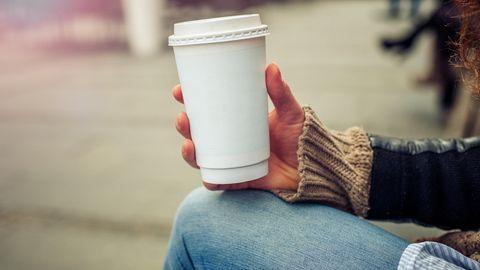 Eine Frau hält einen Pappbecher in der Hand