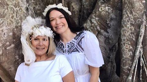 Eine Braut und eine zweite Frau stehen vor einem dicken Baumstamm